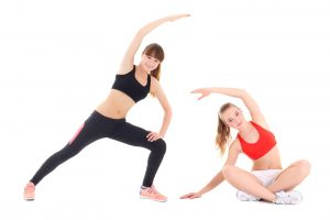 two young sporty women doing stretching exercise isolated on white background